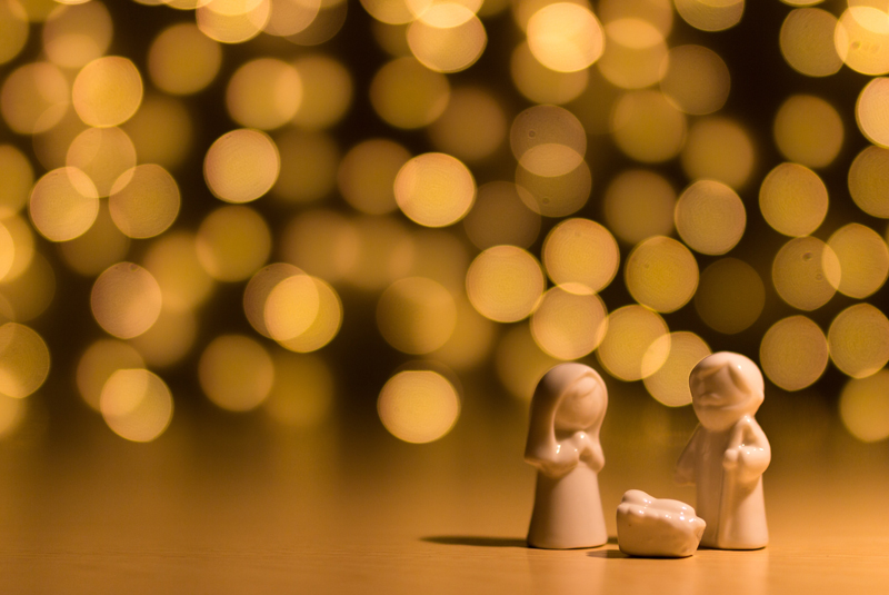 Background of warm yellow christmas lights. in the forground is a small Mary and Joseph figurines standing next to a manger holding baby Jesus.